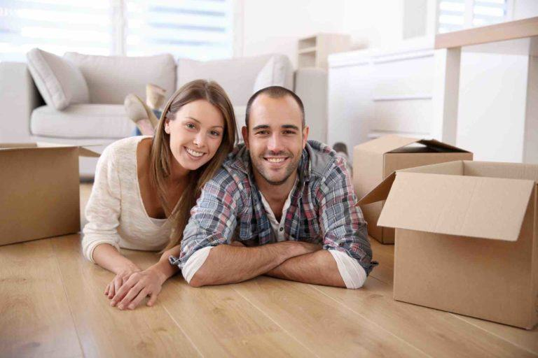 Ehepaar liegt lachend am Boden der Mietwohnung