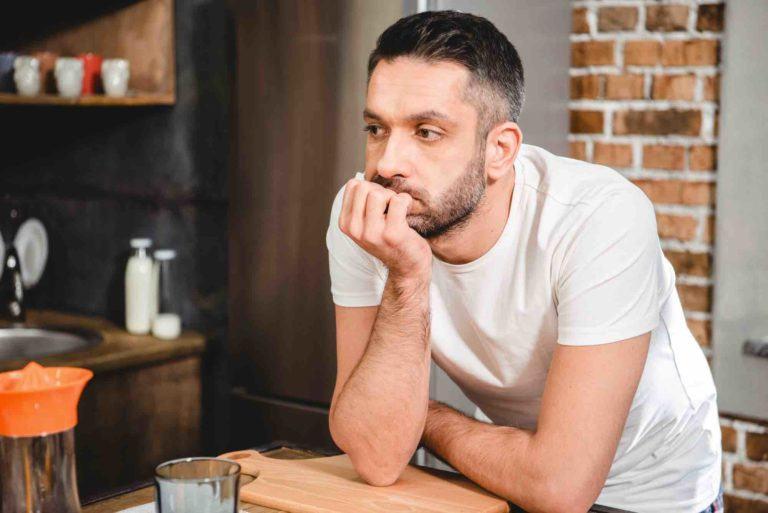 Mann lehnt am Tisch weil er keine Mietkaution erhalten hat