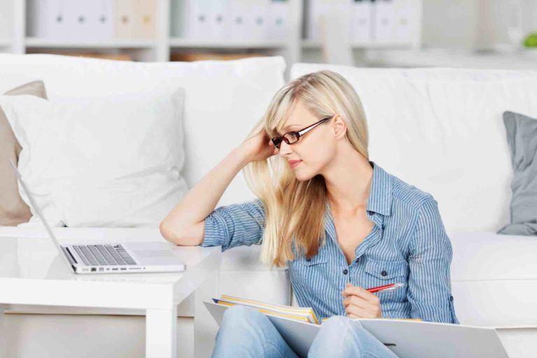 Frau prüft Mietvertrag am Laptop
