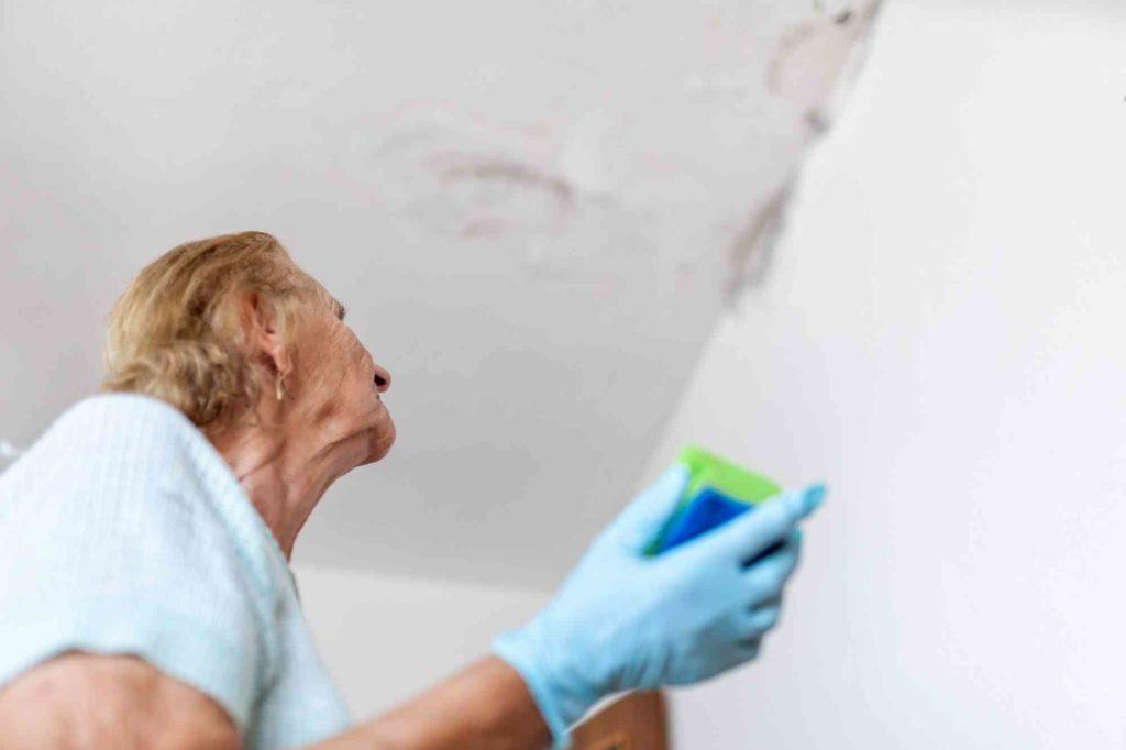 Frau steht unterm Plafond der tropft