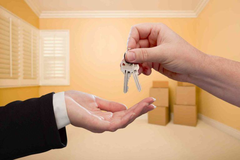 Hand hält Wohnungsschlüssel, die zurückgegeben werden