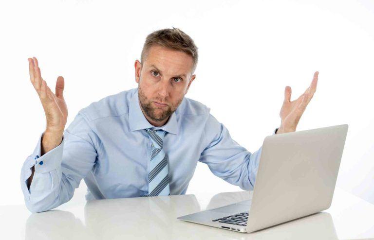 Mann sitzt fragend beim Tisch mit Computer