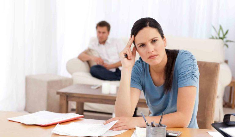 Besorgte Frau sitzt beim Tisch. Ehemann im Hintergrund